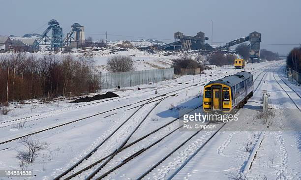 Hatfield colliery, one of the few remaining coal mines in Yorkshre, UK. A passing train on a snowy day adds a theme of transportation