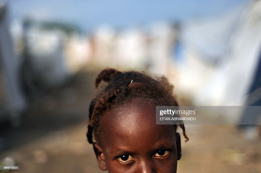 A Hatian girl stands amid tents in a cam : News Photo