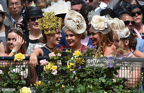 Hats and headresses come in all shapes and sizes as racegoers watch over the mounting yard ahead of the Melbourne Cup at Flemington Racecourse in...