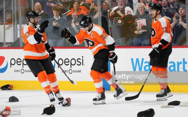 Hats litter the ice as Claude Giroux of the Philadelphia Flyers celebrates his third goal of the game against the New York Rangers with Andrew...
