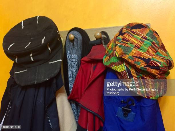 hats, scarves and outerwear hanging on wood pegs  in a home's vestibule - kente fotografías e imágenes de stock