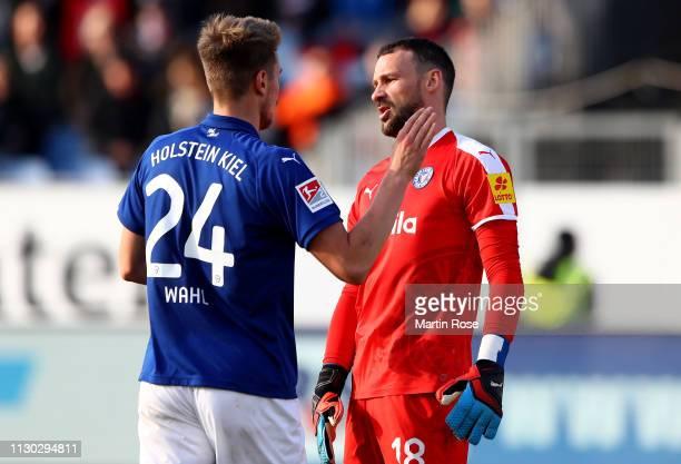 Hauke Finn Wahl of Kiel comforts team mate Ken Kronholm during the Second Bundesliga match between Holstein Kiel and SpVgg Greuther Fuerth at...