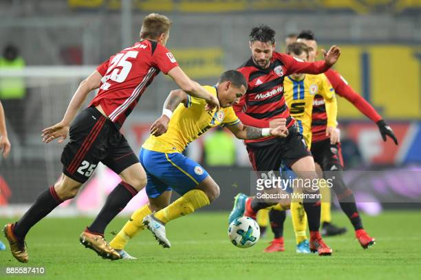 Hauke Wahl and Christian Traesch of Ingolstadt compete for the ball with Louis Samson of Braunschweig during the Second Bundesliga match between FC...