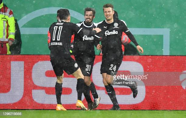 Hauke Wahl of Holstein Kiel celebrates with teammates Fin Bartels and Fabian Reese after scoring their team's second goal during the DFB Cup second...