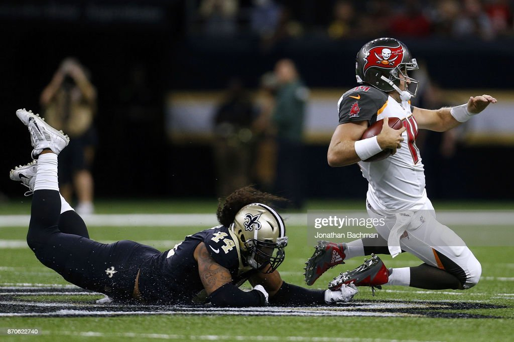 Hau'oli Kikaha #44 of the New Orleans Saints tackles Ryan Fitzpatrick #14 of the Tampa Bay Buccaneers during the second half of a game at Mercedes-Benz Superdome on November 5, 2017 in New Orleans, Louisiana.