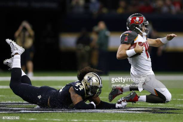 Hau'oli Kikaha of the New Orleans Saints tackles Ryan Fitzpatrick of the Tampa Bay Buccaneers during the second half of a game at MercedesBenz...