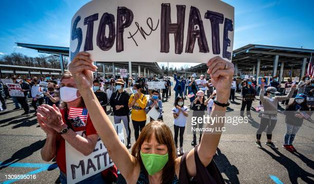 "Long Island resident Patricia Shih holds a sign saying, ""Stop the Hate,"" at the H. Lee Dennison Building in Hauppauge, New York during a rally to..."