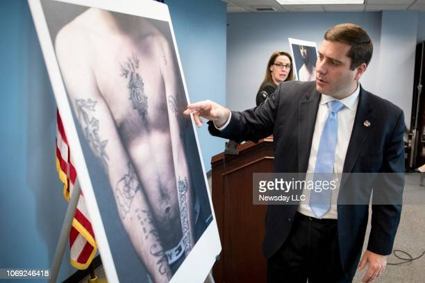 Suffolk County District Attorney Timothy Sini points out tattoos of a convicted MS-13 gang member who used the threat of violence to attempt to...