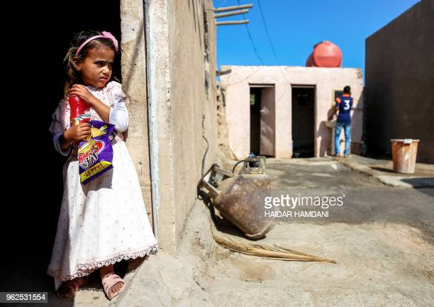 Haura a fouryearold Iraqi child with a rare skin congenital disease that covers much of her upper body in black marks and hair stands through the...