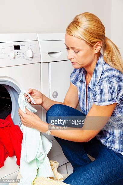 Hausfrau mit Wäsche an der Waschmaschine liest die Wascheinleitung auf dem Etikett eines Kleidungsstücks
