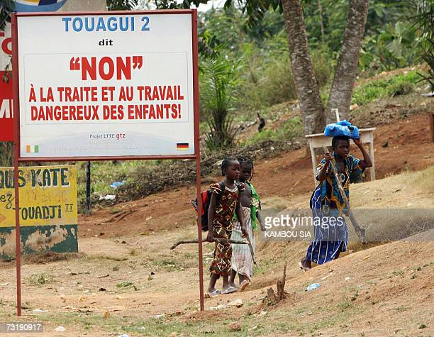 FRENCH Hausse du trafic d'enfants vers les plantations de cacao ivoiriennes Children stand next to a billboard set up on a road of a cocoa bean...
