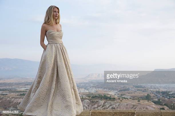 haute couture model poses above desert landscape - strapless evening gown stock pictures, royalty-free photos & images
