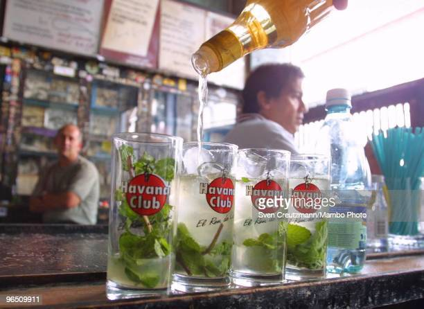 Havana Club rum is being poured into glasses to make the Mojito a typical Cuban rum cocktail stand at the bar of the Bodeguita del Medio bar and...