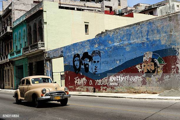 an old American car driving past a fresco showing heroes of the Cuban revolution Havana