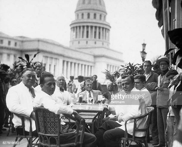 An outdoor cafe with a view of the Capitol Building in the background Men are seated in the cafe enjoying refreshing beverages Photograph circa...