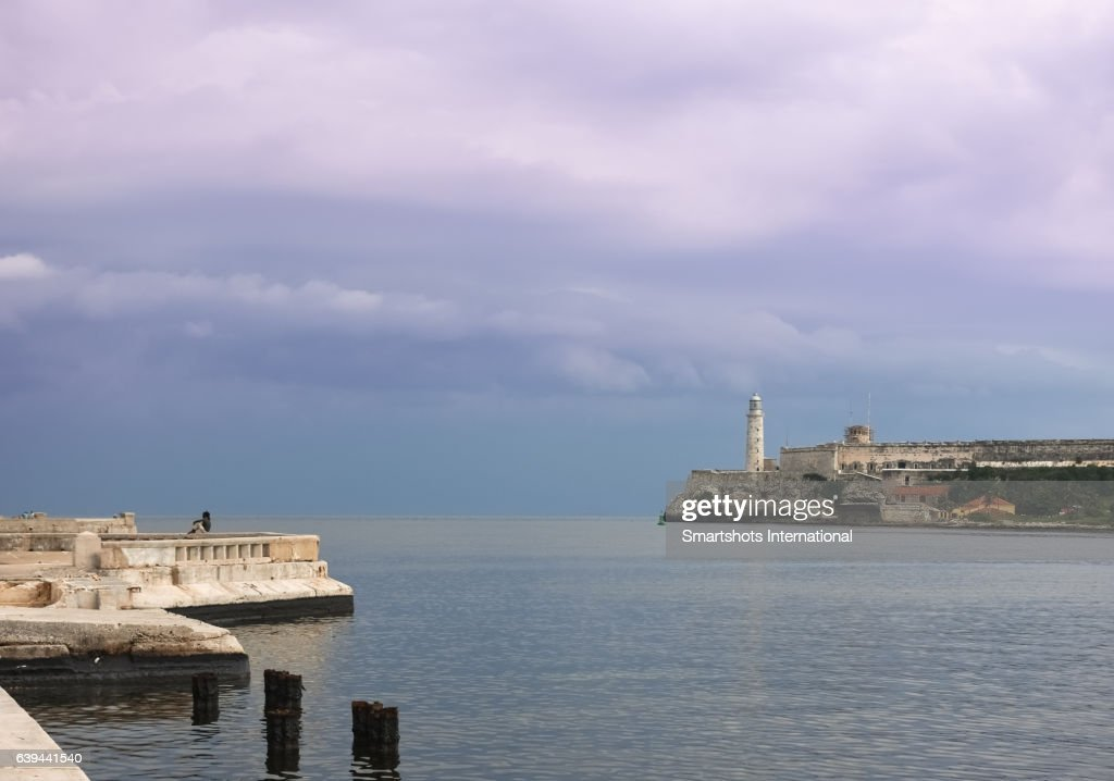 Havana Malecon with Morro lighthouse and a lonely, unrecognizable person relaxing by the sea, Cuba : Photo