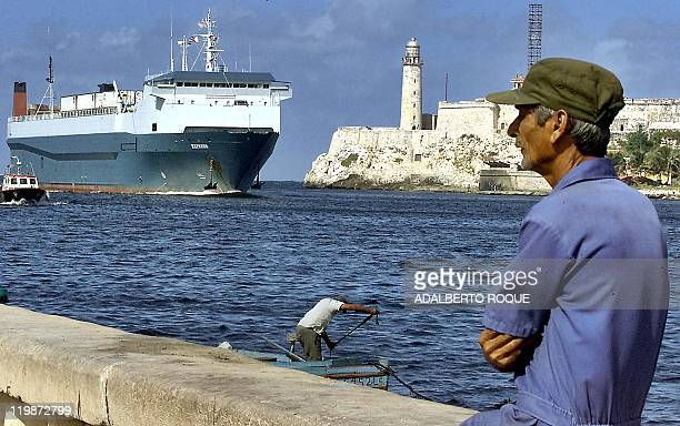A Havana resident watches as the Express container ship docks 16 December with 20 containers of frozen chicken worth about 300000 USD shipped from...