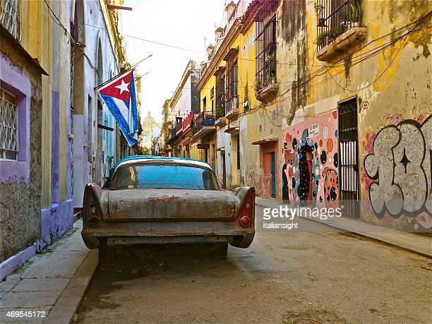 havana street con coche viejo y bandera cubana. - bandera cubana fotografías e imágenes de stock