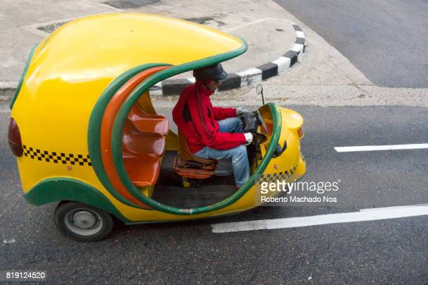 Havana tourism 'cocotaxi' Man in red jacket driving small covered yellow green auto rickshaw on a cemented grey road