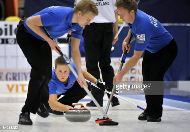 Havard Vad Petersson of team Norway eyes the stone while Christoffer Svae and Torger Nergard sweeps in the final between Scotland and Norway on...