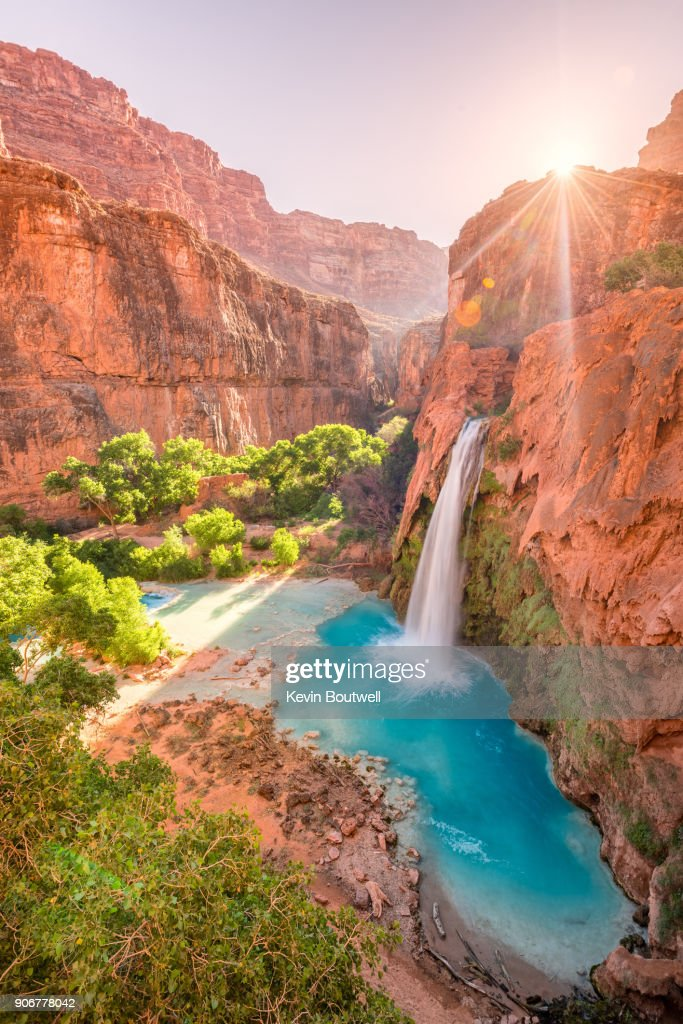 Havasu Falls in Arizona plunges in turquoise waters as the sun rises above the cliffside : Stock Photo
