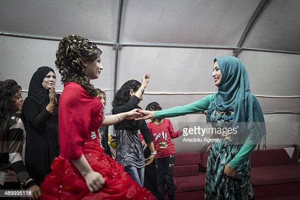 Havazi Hilen a refugee girl who fled Syria three months ago with her family dances with her relatives during her henna night at a tent city in the...