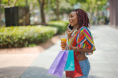 happy woman using phone after shopping
