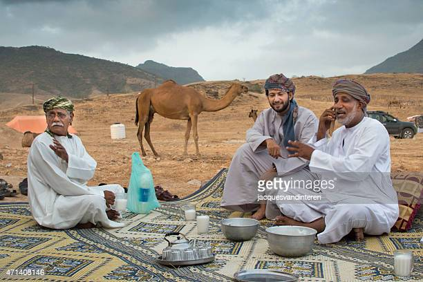 having a chat in the desert near salalah, oman - bedouin stock pictures, royalty-free photos & images