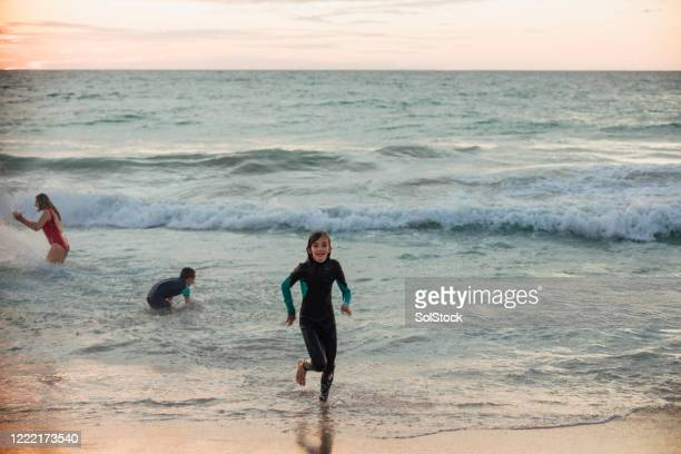 having a dip at dusk - sea swimming stock pictures, royalty-free photos & images