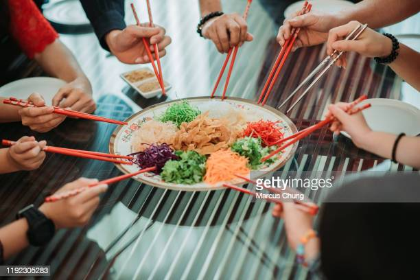 "having chinese new year food, raw fish salad ""yusheng"" with group of hands holding chopstick during reunion dinner - simple living stock pictures, royalty-free photos & images"