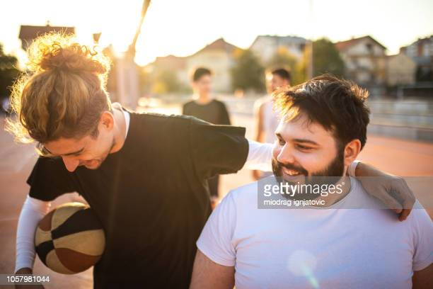 having fun and laughing cheerfully at basketball court - male friendship stock pictures, royalty-free photos & images