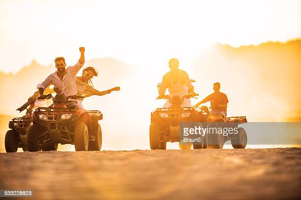 Having fun on quad bikes at sunset.