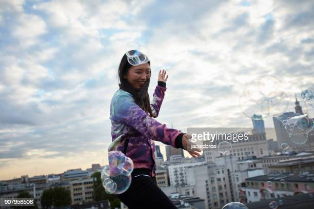 Having fun with soap bubbles. Asian woman standing on the rooftop