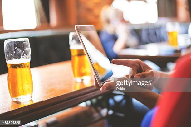 Having glass of beer and using digital tablet