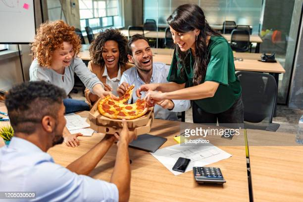 having lunch together. happy multicultural team eating pizza and communicating with each other while sitting in the modern office - funny customer service stock pictures, royalty-free photos & images