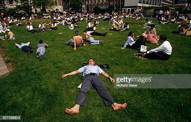 Having removed his shoes and socks and with his wallet sitting on his stomach a city office workers stretches out over the lush grass during a hot...