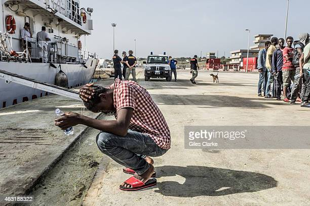 Having sailed in a cramped boat with no amenities and squalid conditions a rescued North African migrant washes himself with a donated bottle of...