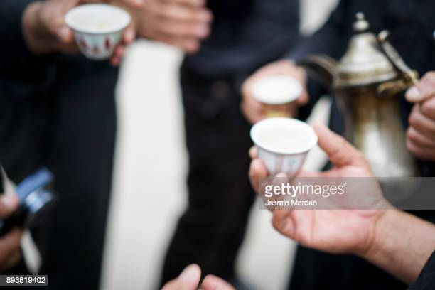 having traditional arabian coffee with friends - bahrain national day stock photos and pictures