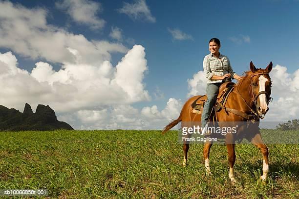 hawai, kauai, woman riding horse in field with king kong's profile in background - equitación fotografías e imágenes de stock