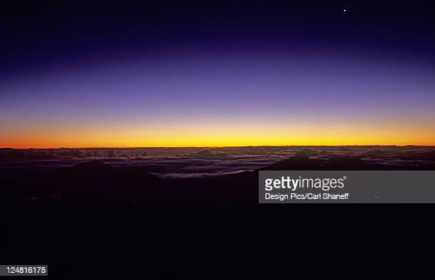 Hawaii, a band of bright yellow light above the clouds at sunset as the darkness of night closes in.