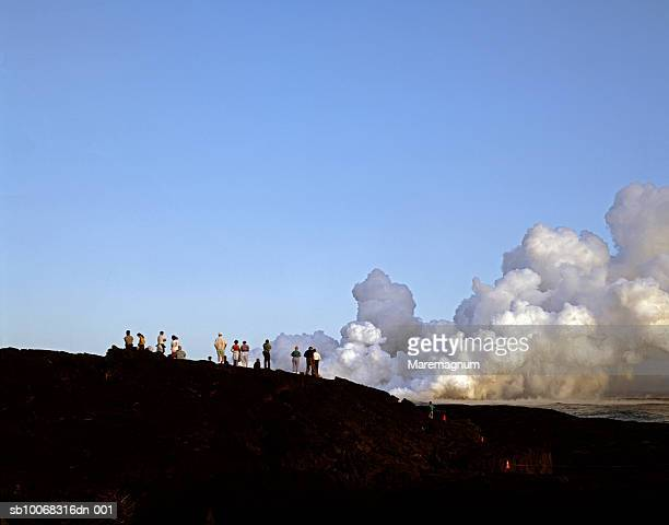 usa, hawaii, big island, volcanoes national park, people standing and watching kilauea eruption - ハワイ火山国立公園 ストックフォトと画像