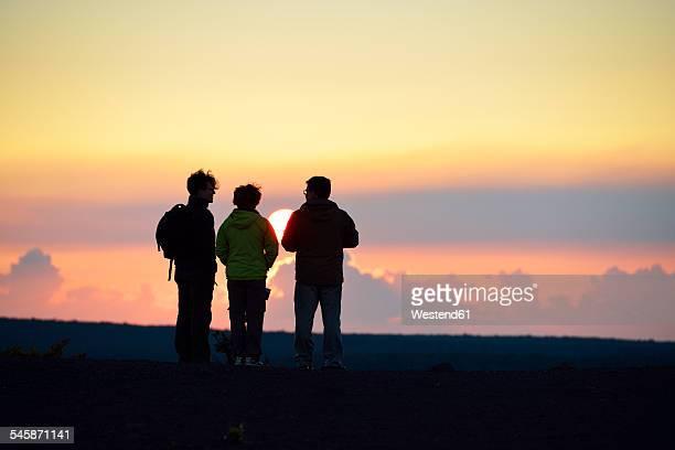 USA, Hawaii, Big Island, Volcanoes National Park, three persons watching sunset at Kilauea Iki