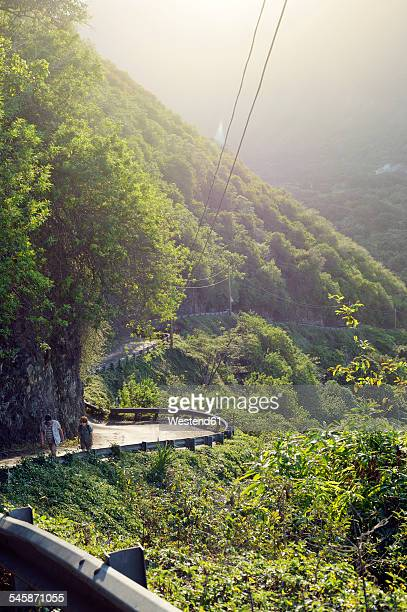 usa, hawaii, big island, waipio valley, two hikers walking at evening light - waipio valley stockfoto's en -beelden