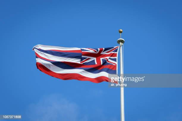 hawaii flag flying on blue sky - hawaii flag stock pictures, royalty-free photos & images