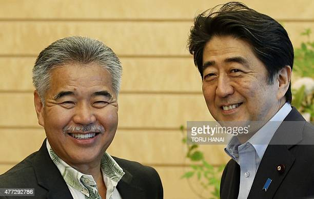 Hawaii Governor David Ige shakes hands with Japan's Prime Minister Shinzo Abe at Abe's official residence in Tokyo on June 16 2015 AFP PHOTO / POOL