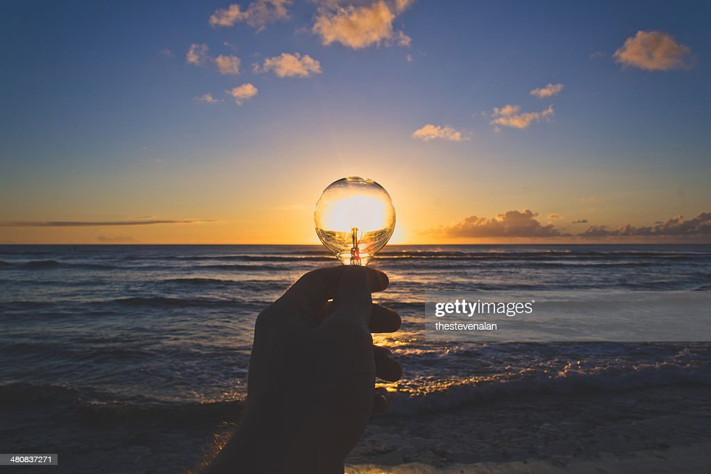USA, Hawaii Islands, View of hand holding lightbulb at sunset : Stock Photo