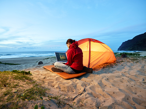 USA, Hawaii, Kauai, Polihale State Park, woman using laptop at tent on the beach at dusk - gettyimageskorea