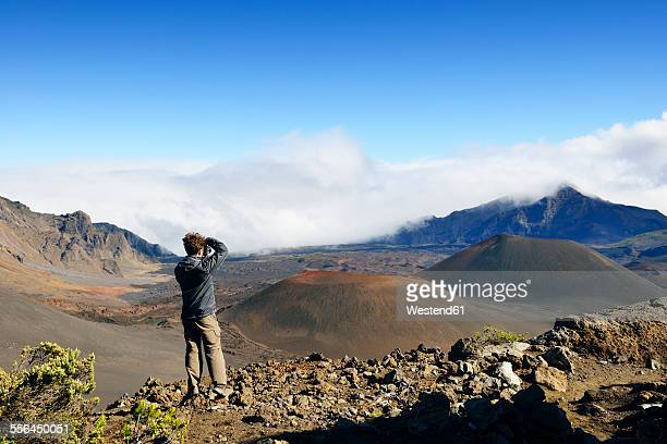 USA, Hawaii, Maui, Haleakala, man taking picture of volcanic landscape with cinder cones