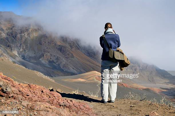 USA, Hawaii, Maui, Haleakala, woman taking picture of volcanic landscape with cinder cone