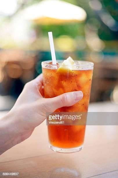 USA, Hawaii, Maui, hand holding iced tea with lemon
